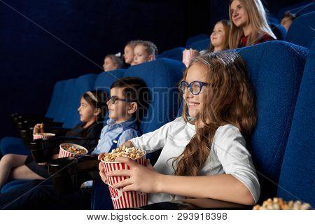 Happy, Joyful Kids Sitting In Dark Blue, Comfortable Chairs In Modern Cinema Theatre, Watching Movie