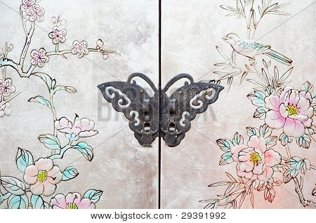 Beautiful butterfly lock on the door of  old Chinese furniture.