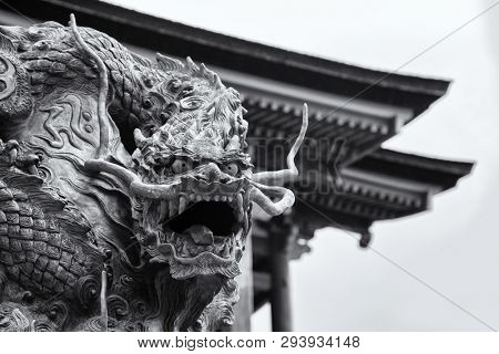 Black and white closeup of an ancient dragon statue outside of the Kiyomizu-dera temple on Mount Otowa. Image taken from a public street.
