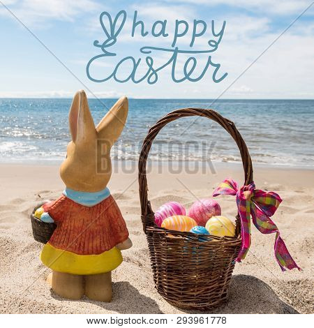 Easter Bunny With Basket And Color Eggs On The Sandy Beach Near Ocean. Hand Drawn Happy Easter Typog