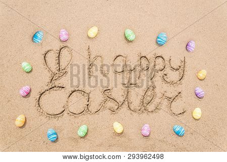 Happy Easter Background With Eggs On The Sandy Beach Near Ocean. Hand Drawn Happy Easter Typography