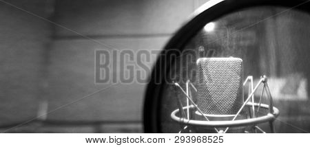 Studio Microphone With Shock Mount And Pop Filter On Professional Tripod In Acoustic Foam Room For B
