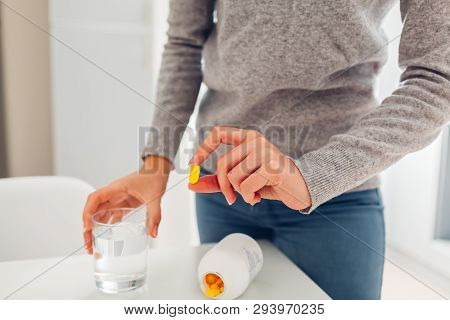 Woman Taking Pills With Glass Of Water On Kitchen. Healthcare And Medicine