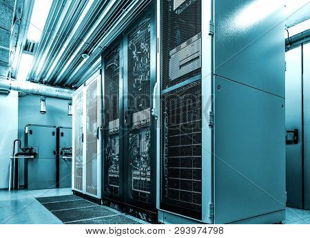 Datacenter Server Racks With Network Computers In Neon Blue Toning. Room With Several Of Mainframe H