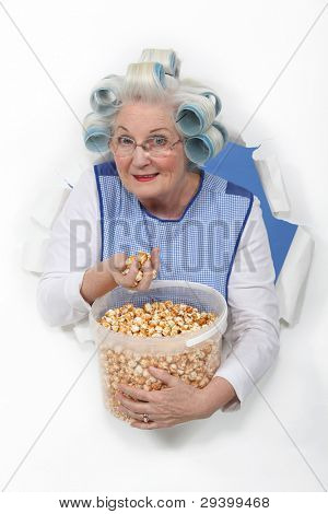 senior woman with curlers in her hair eating popcorn