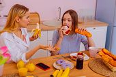 Sister feeling shocked seeing younger sister eating sugary food poster