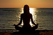 Silhouette of woman in yoga lotus meditation position front to seaside poster