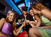 Happy girls having fun in limo, drinking champagne.? poster