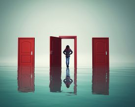 Woman On Water In Front Of Different Doors. The Concept Of Choosing The Right Way