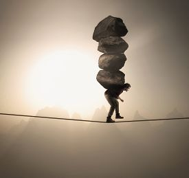 Man Carries A Stack Of Big Rocks While Balancing On A Rope At High Altitude .