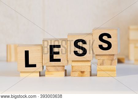 Less Word On Wooden Cubic Blocks With Letters And Stack Of Coins On It. Selective Fofus. Spend Less
