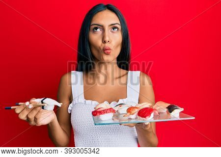 Young brunette woman eating butterfish sushi using chopsticks making fish face with mouth and squinting eyes, crazy and comical.