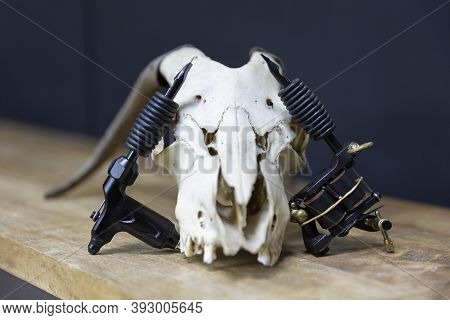 Composition With Two Different Models Of Tattoo Machines Resting On A Goat Skull In A Tattoo Studio.