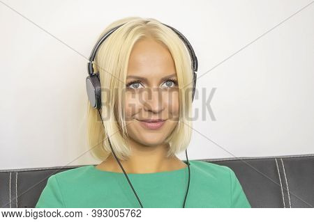 A Young Woman 25-30 Years Old Sits On A Dark Sofa With Headphones And Listens To Music 1.