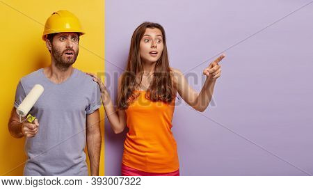 Home Renovation, Painting And Decoration Concept. Shocked Husband Wears Helmet, Holds Paint Roller,