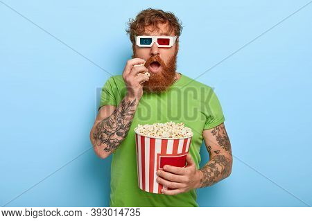 Isolated Shot Of Handsome Man Has Tattoo, Ginger Hair, Watches Movie, Involved With Story, Swallows