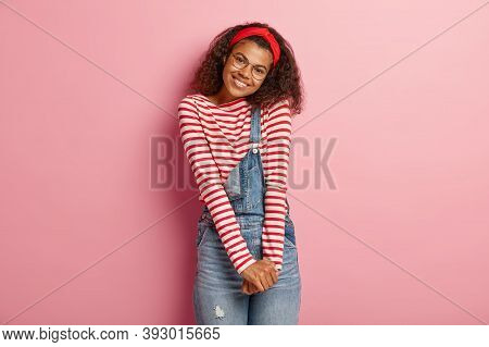 Isolated Shot Of Shy Smiling African American Woman Keeps Hands Together, Tilts Head, Dressed In Str