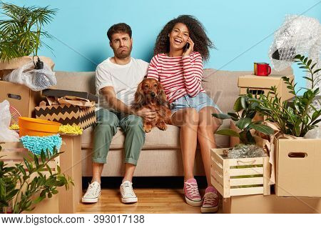 New Life Stage Concept. Spouses Move In New House, Take Mortgage Or Loan Sit On Sofa In Messy Room W