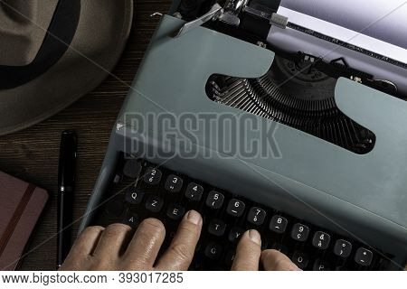 A Man While Writing With An Old Typewriter