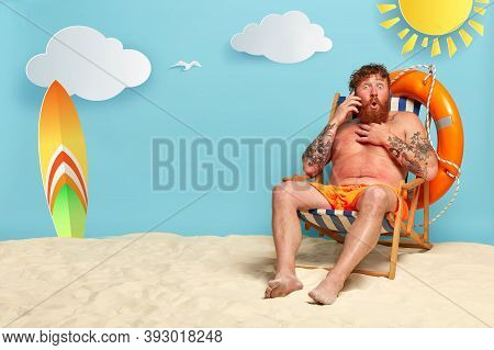 Shot Of Astonished Bearded Guy Has Red Sunburned Skin, Talks On Smartphone, Hears Shocking News From