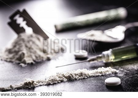 Cocaine With Rows, Rows And Lines Of Powder To Be Tested, With A Drool Blade Beside It And Syringes