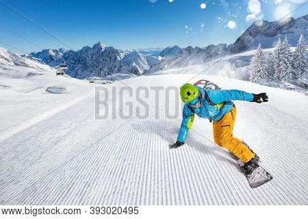 Snowboarder going downhill during sunny day in high mountains