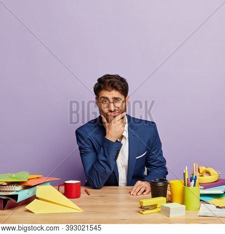 Thoughtful Confused Employee Wears Formal Clothes, Poses In Coworking Space, Thinks About Business D