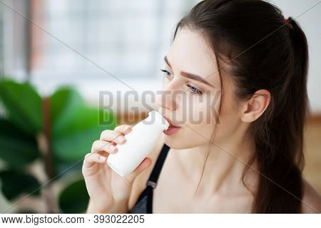 Young Beautiful Woman Drinking From Plastic Bottle Of Yogurt