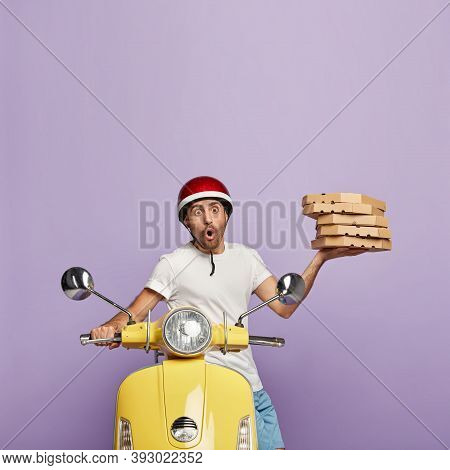 Photo Of Scared Man Distributes Fast Food, Carries Cardboard Containers With Pizza, Wears Helmet, St