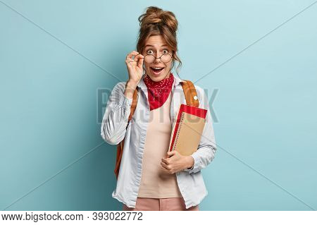 Surprised Happy Female Student Looks Through Glasses, Holds Hand On Frame, Carries Spiral Notebook A