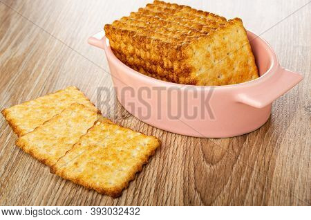 Stack Of Crunchy Cookies With Sesame In Pink Bowl, Three Crackers On Wooden Table