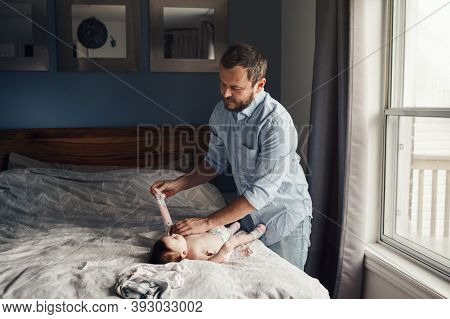 Middle Age Caucasian Father Changing Diaper Clothes For Newborn Baby Daughter Son. Man Parent Taking