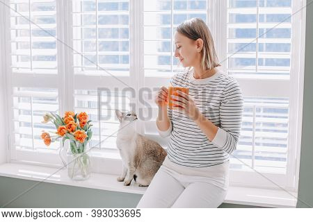 Beautiful Happy Middle Age Woman Sitting On Windowsill At Home And Looking At Cat. Young Woman With
