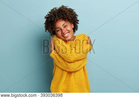 Lovely Happy African American Woman Daydreams, Embraces Herself, Recalls Romantic Date, Feels Comfor
