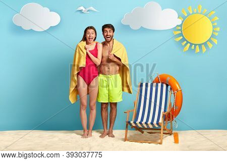 Traveling Couple Stand Together Under One Towel, Dressed In Beachwear, Relax At Paradise Beach, Have