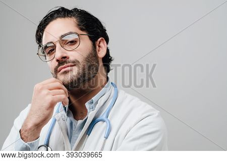 Skilled Professional And Adult Physician Dressed In White Labcoat Poses With Hand Under His Chin In