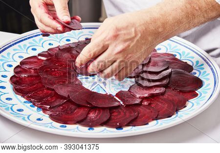 The Chef Prepares Beetroot Carpaccio On A White Plate.