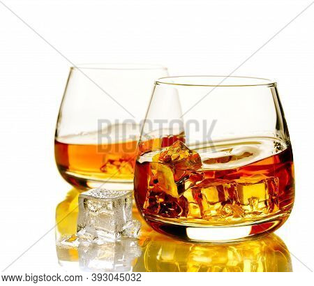 Two Glasses Of Scotch Whiskey And Ice On A White Background With Reflection. Close-up