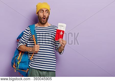 Vacation And Traveling Concept. Surprised Unshaven Guy Poses With Rucksack On Shoulders, Wears Strip