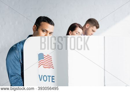 Indian Man Looking At Camera From Polling Booth Near Multicultural Electors On Blurred Background