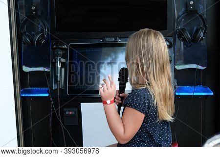 Little Girl Singing In Individual Karaoke Room In Shopping Mall. Consumer Can Insert Coins Or Mobile