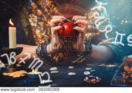 Astrology And Divination. A Fortune Teller Holds A Red Apple In Her Hands. On The Sides Of The Image
