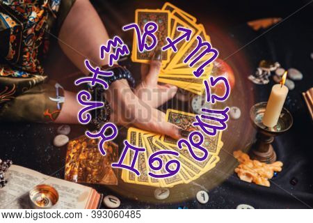 Astrology And Esotericism. A Fortune Teller Holds A Fan Of Tarot Cards. On The Table Are Runes And C