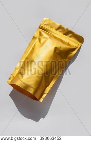 Golden Metalized Pouch Bag With Coffee Beans Top View With Shadow Isolated On White Background. Food