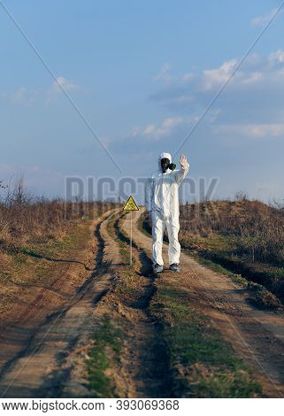 Ecologist In White Coverall, Gas Mask And Gloves Standing On Village Road In The Field Next To Toxic