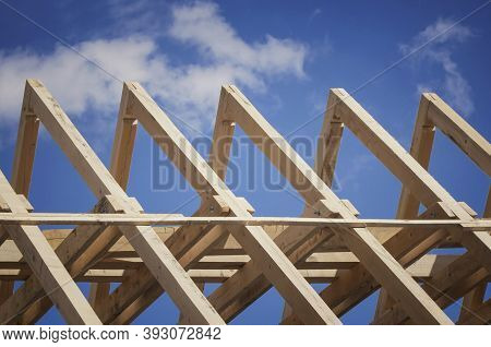 Roof Construction. New Residential Construction Home Framing Against A Blue Sky.
