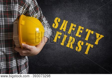 Safety First Concept. Safety First Stencil Print On The Black Concrete Wall. Construction Worker Wit