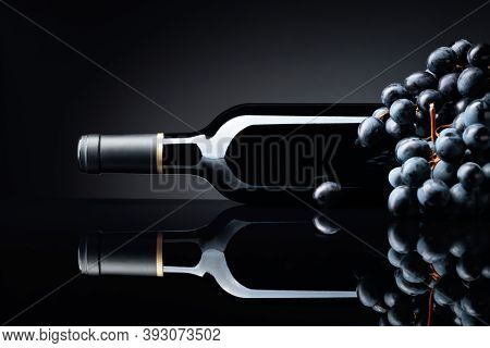 Bottle Of Red Wine And A Bunch Of Grapes On A Black Reflective Background. Selective Focus, Copy Spa