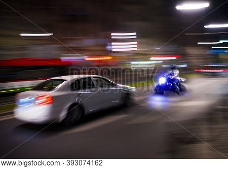 Dangerous City Traffic Situation With A Motorcyclist And A Car In Motion Blur. Defocused Image