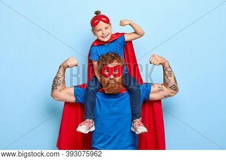 Strong Powerful Dad And Little Female Child On His Shoulders Show Muscles, Ready To Defend You And S